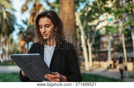 Pretty Woman In Business Suit And Wireless Earphones Selects Music Using Laptop Computer While Relax