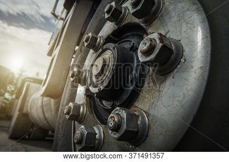 Heavy Duty Transportation Theme. Aged Semi Truck Wheel And Rusty Nuts Close Up. Industrial Concept.