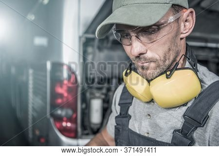 Coach Buses And Trucks Mechanic Job. Caucasian Bus Technician In Eye Protection Glasses During Sched