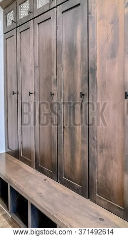 Vertical Crop Brown Wooden Vintage Cabinet With Glass Panes Doors And Open Bottom Shelves