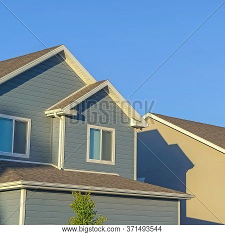 Square Homes With Horizontal Wall Sidings And Front Gable Roofs Againts Clear Blue Sky