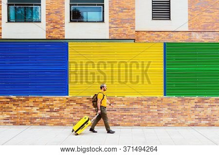 Man Traveling With Suitcase And Backpack On The Street