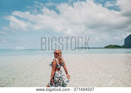 A Girl In A Swimsuit Stands In The Ocean And Waits For A Seaplane Against The Background Of Mount Le