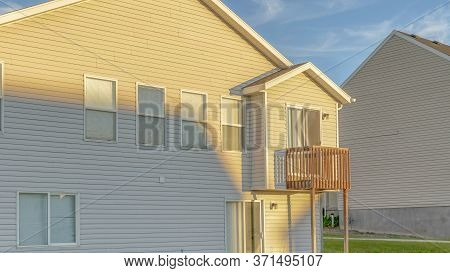 Panorama Frame Home With White Wall Siding Gable Roof And Small Balcony Viewed On A Sunny Day
