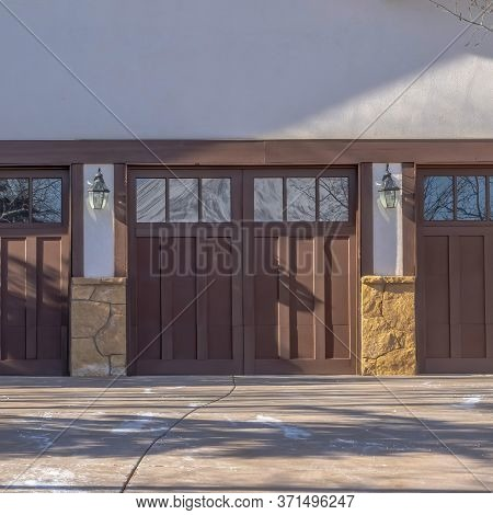 Square Crop Driveway Leading To Three Wooden Garage Doors With Glass Panes In Park City Utah