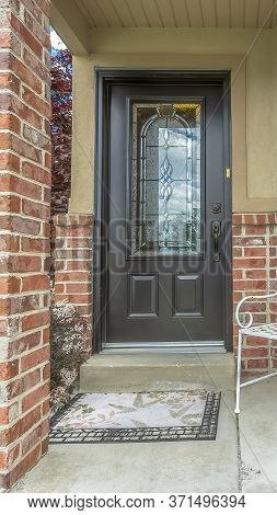 Vertical Front Door With Decorative Glass Pane At The Facade Of Home With Red Brick Wall