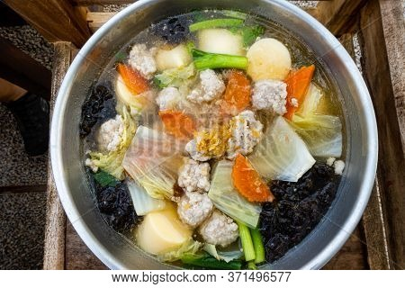 Clear Soup With Tofu, Minced Pork And Various Vegetables In A Metal Pot.