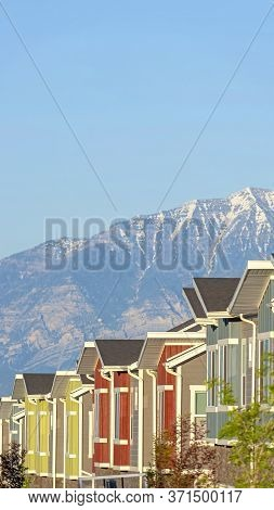 Vertical Snowy Mountain And Blue Lake View Behind Townhouses With Colorful Exterior Walls