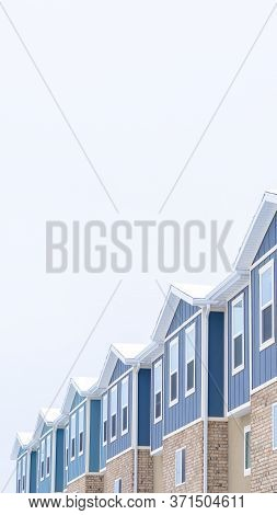 Vertical Crop Snowy Gable Roofs At The Facade Of Townhome With Brick Wall And Vertical Siding