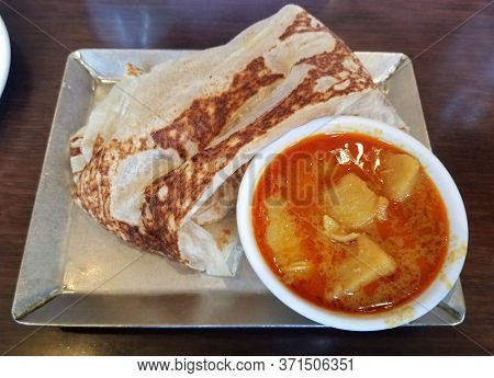 Malaysian Pancake, Also Known As Roti Canai, With A Side Of Curry Gravy