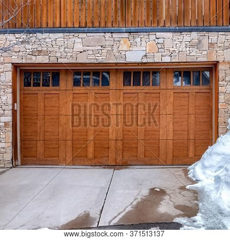 Square Crop Brown Wooden Glass Paned Garage Door Against Stone Wall Under Balcony Of Home