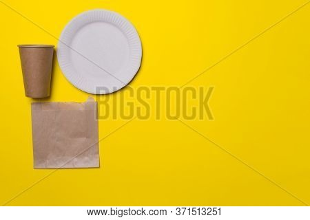 Eco-friendly Kitchen Ware, Plate, Cup, Bag, In Yellow Colored Paper Background With Copy Space. Top