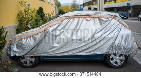 car is protected from weather by tarpaulin.