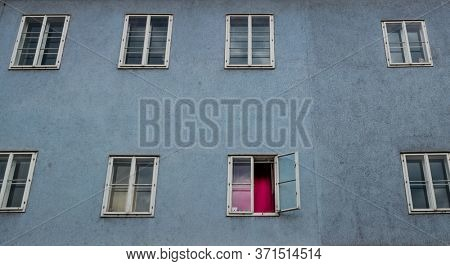 a desolate facade in an old apartment building. window with red