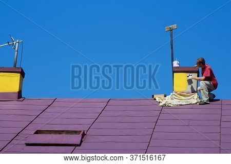 Chimney Painting, Painter Paints The Chimney On The Roof In Yellow