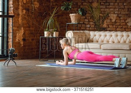 Girl Seating On Yoga Mat In Sport Outfit With Camera