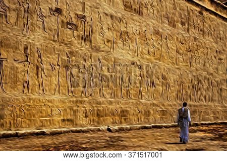 Wall With Hieroglyphs Carved By The Ancient Egyptians In The Edfu Temple And Visitor Walking, Near A