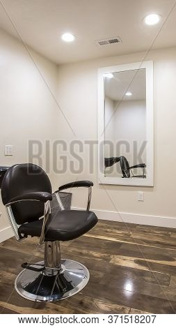 Vertical Crop Hairdresser Chair And Backwash Shampoo Bowl Inside Salon With Bench And Mirror