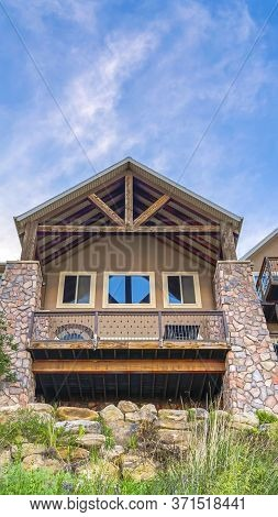Vertical Gable Roof With Wooden Beams Over Balcony And Porch With Square Stone Columns