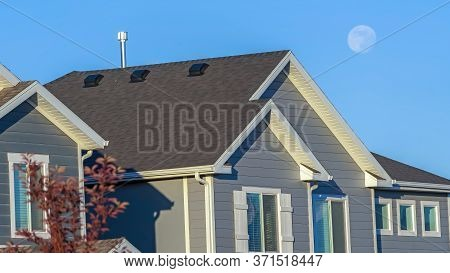 Panorama Sunlit Home With Dark Pitched Roof Over Horizontal Gray Wall Siding And Windows