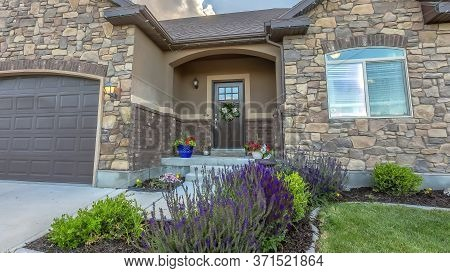 Panorama Crop Facade Of Home With Lush Yard In Front Of Stone Wall And Gable Roofs