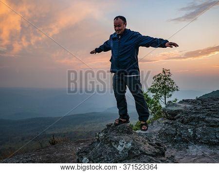 Asian Fat Trekker With Sunset Light On Yeabmek Cliff Phu Kradueng Mountain National Park In Loei Cit