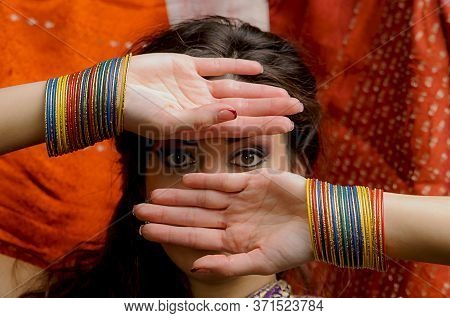The Young Dark-haired Woman In Indian Sari And Colorful Bangles Looking Through His Hands. Indian St