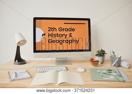 Background Image Of Minimal Workplace Setting With Computer On Desk And Online School Website On Scr