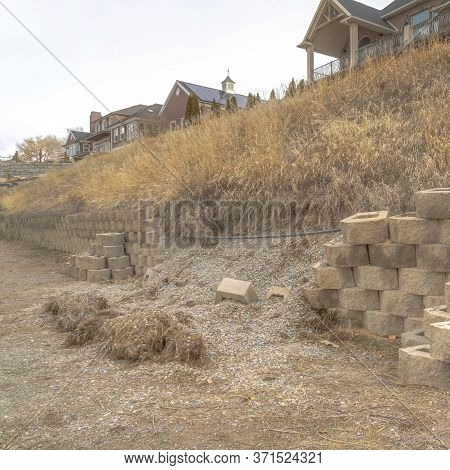 Square Frame Damaged Stone Blocks Retaining Wall Lining A Hill With Homes Under Cloudy Sky