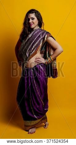 The Young Dark-haired Woman In A Beautiful Indian Saris And Colorful Bracelets Posing Barefoot Putti