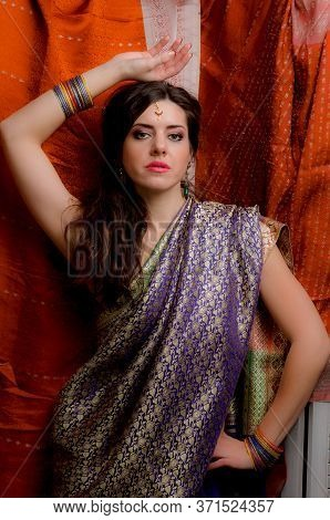 The Young Dark-haired Woman In The Rich Indian Sari Looks Thoughtfully Holding Up One Arm Above The