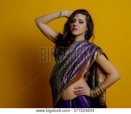 The Young Dark-haired Woman In A Bright Indian Saris And Colorful Bracelets Raised Her Hand To The H