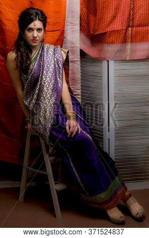 The Young Dark-haired Woman In The Rich Indian Saris Looks Attentively Sitting On A Folding Ladder O
