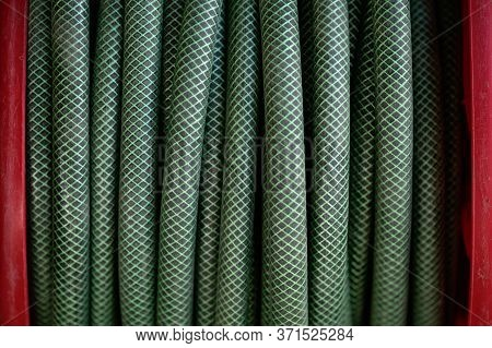 A Green Garden Hose Wound Around A Red Bobbin. Hose Reel. Garden Watering Tool Close-up. Checkered T