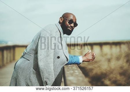 Portrait Of A Handsome Bearded Bald African Man In Sunglasses And Coat Leaning On A Wooden Fence Out