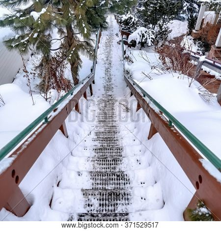 Square Grate Metal Tread Stairway On Hill Slope Blanketed With Snow During Winter