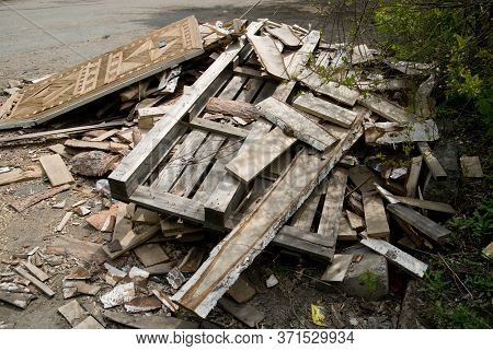 Background Of Sawn Birch Boards, Trash And An Old Door Piled In A Pile.