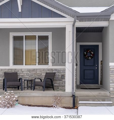 Square Home Facade With Gable Roof Front Porch And Door With Wreath In Winter