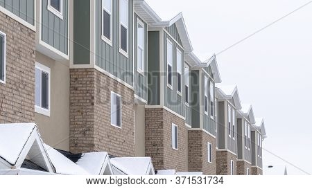 Panorama Frame Townhome Facade With Snowy Gabled Roof At The Entrance In Winter