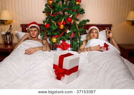 Young couple in Santa's hats  with glass of champagne lying on bed with Christmas tree