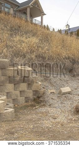 Vertical Frame Damaged Stone Blocks Retaining Wall Lining A Hill With Homes Under Cloudy Sky