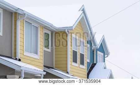 Panorama Crop Townhome Exterior With Snowy Gable Valley Roof Against Overcast Sky In Winter