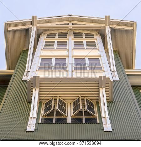 Square Home With Cottage Pane Windows And Gable Roof Viewed From Below Against Sky