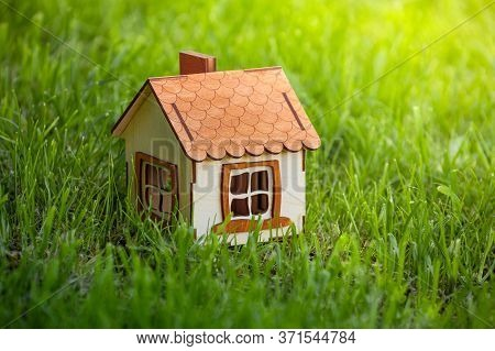 Small  Wooden House Model On The Grass In Garden, Country House, Architecture And Construction Of Co