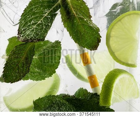 Close Up View Of The Cold And Fresh Lemonade With Lime Slices, Ice Cubes And Mint Leaves. Texture Of