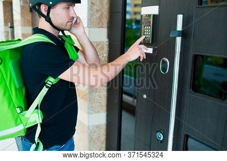 Food Delivery Concept. Food Delivery Man Ringing On Intercom