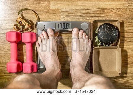 A Man Is Weighed On A Scale And Next To It Are Dumbbells And A Black Burger