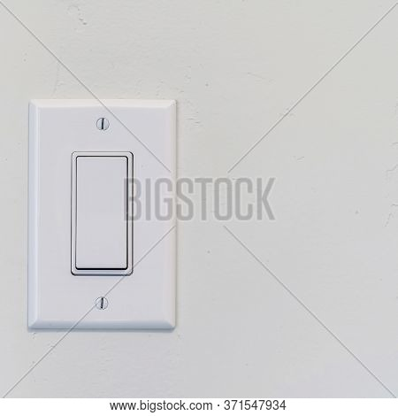 Square Electrical Rocker Light Switch With Flat Broad Lever On White Interior Wall