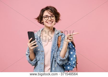 Smiling Girl Student In Denim Clothes Glasses Backpack Isolated On Pastel Pink Background. Education