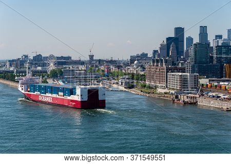 Montreal, Canada - 14 June 2020: View Of Montreal From Jacques Cartier Bridge As A Cargo Ship Is Hea